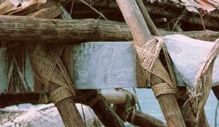 Figure 13. The hakatu (outrigger struts) and lashing. Taumako call the diamond pattern in the middle of the lashings umu (oven, imu in Hawaiian) for its resemblance to a traditional cooking pit. Many such lashings require more than two hands for their accomplishment; yet another example of the ways in which voyaging canoe builders must work in concert. (Photo by H. M. Wyeth)