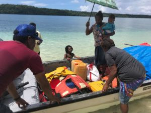 Family packing OBM canoe for sea crossing