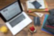 Desk with laptop, paperwork, pencils, notebook