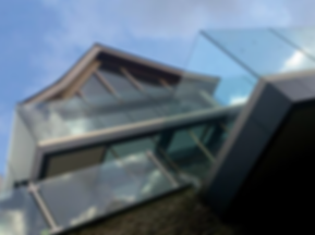 Angled shot of Rockvale House in Dartmouth showing frameless glass balustrade and oak frame with blue sky behind