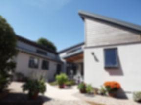Architect designed courtyard house in Newton Poppleford, Devon whowing white render, western Red Cedar Cladding and blue