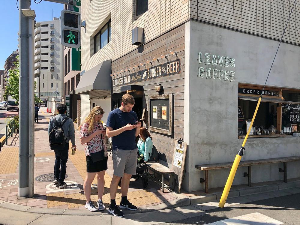 コーヒースタンドの前でスマートフォンを片手に散策中の外国人旅行者