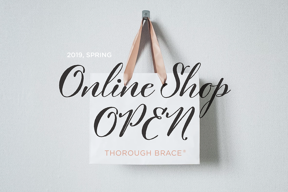a shopping bag printed THOROUGH BRACE brand logo and words online shop open