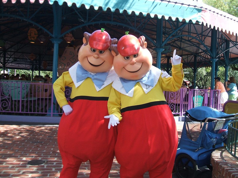 Costumed characters Tweedle Dum and Tweedle Dee pose before a carousel at Walt Disney World's Magic Kingdom.