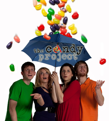 """Cathy, a woman and two men stand under an umbrella with logo that reads """"The Candy Project"""" with jelly beans raining down on them."""