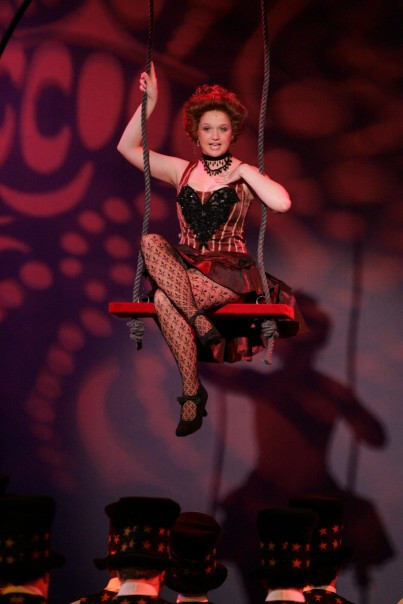Cathy dressed in vaudeville costume, singing from a swing on a stage above the heads of other actors