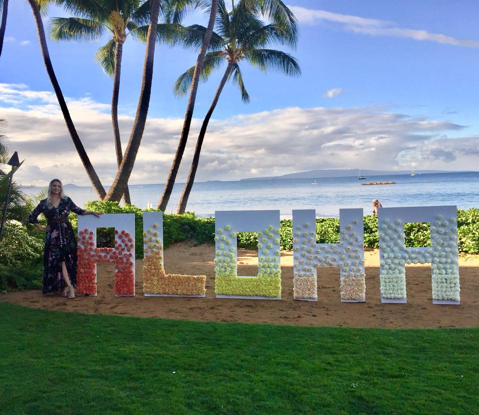 Cathy stands on a beach with palm trees and ocean in the background. In the foreground are large marquee style letters that say ALOHA and are covered in flowers.