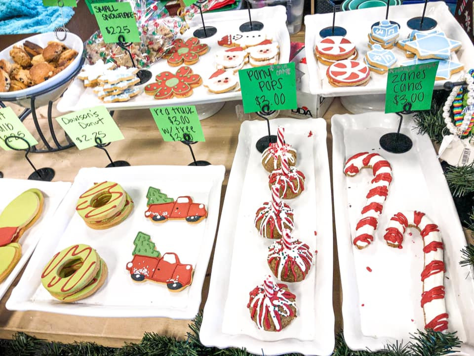 Store display of various dog bakery items featuring Christmas decorated cookies and treats.