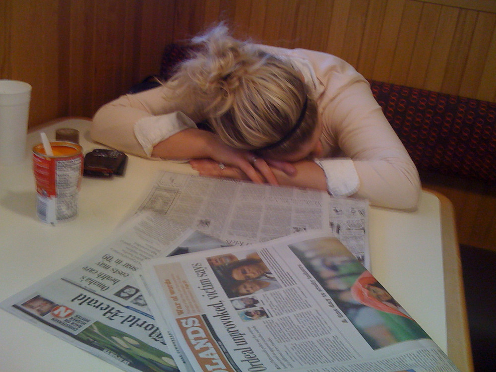 Woman at diner with her head down, asleep at the table with newspapers strewn about.