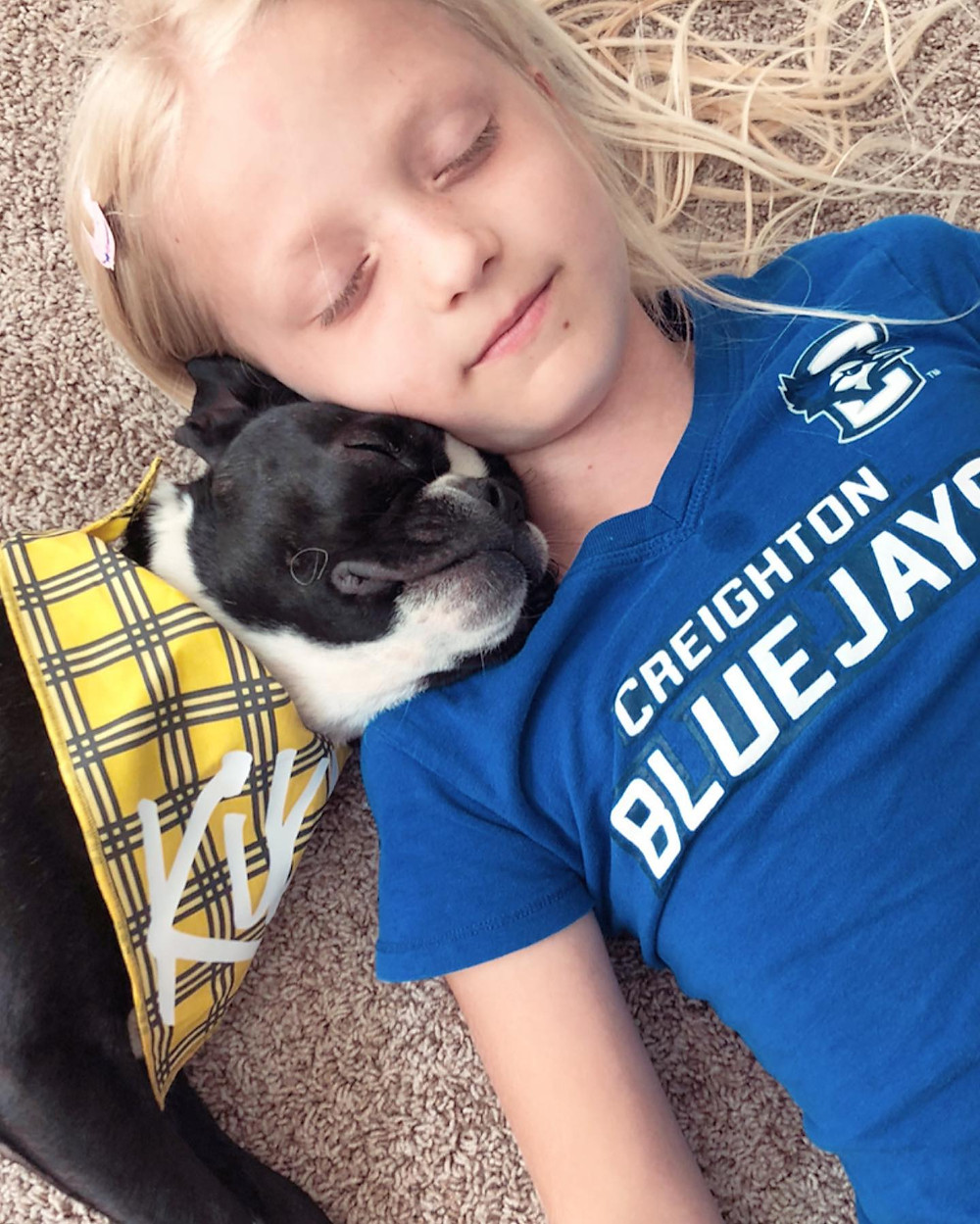 Kiki and small girl, both asleep. Kiki rests his head on her shoulder.
