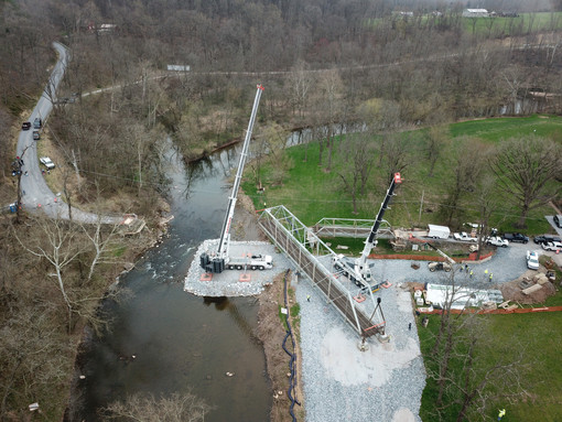 Using two cranes, crews prepare to lift the truss