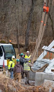 Crews attach each crane to the bridge