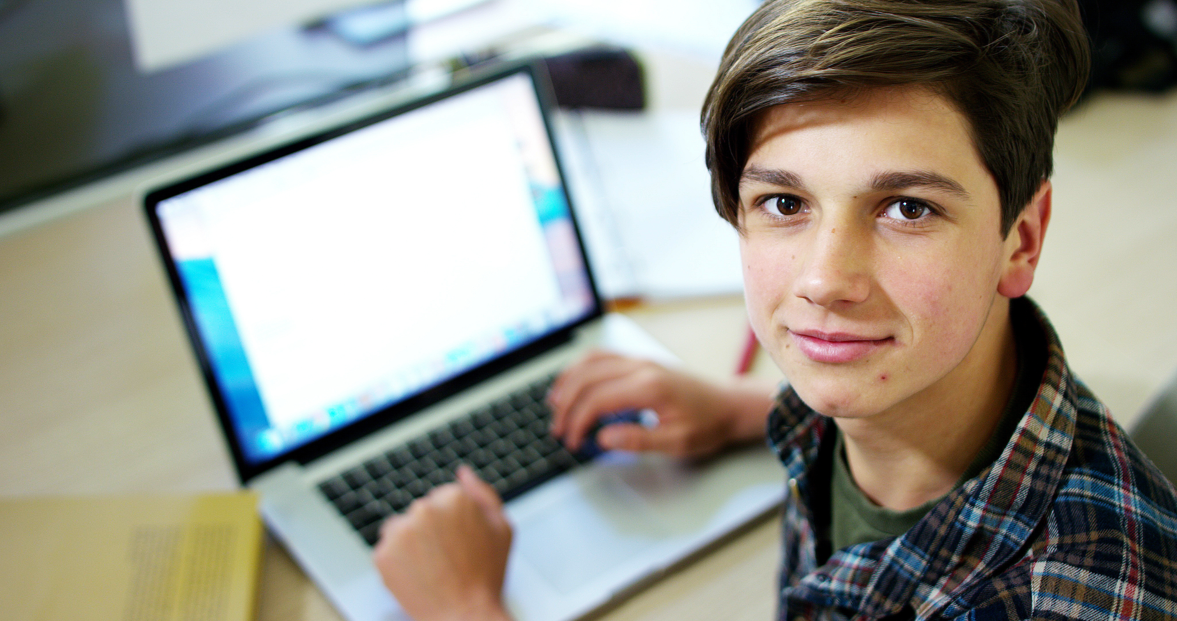 Young boy student, studying computer and