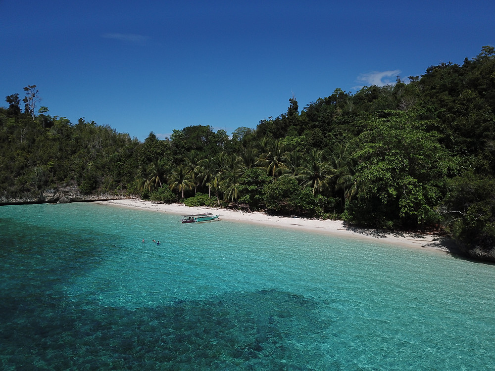 Beautiful white-sandy beach at Togian Islands. Crystal blue water with a boat and snorkellers set in the front.