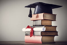 Graduation hat and diploma with book on