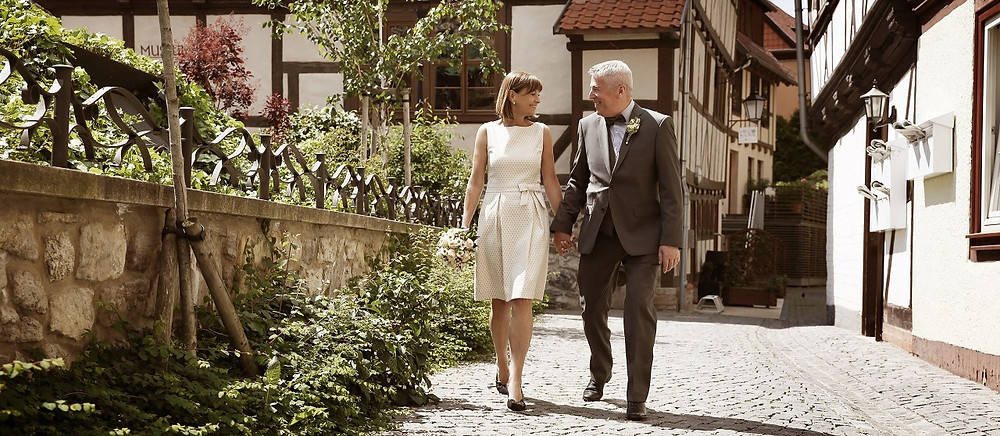 Hochzeit laufen Hand in Hand durch eine Historische Stadt