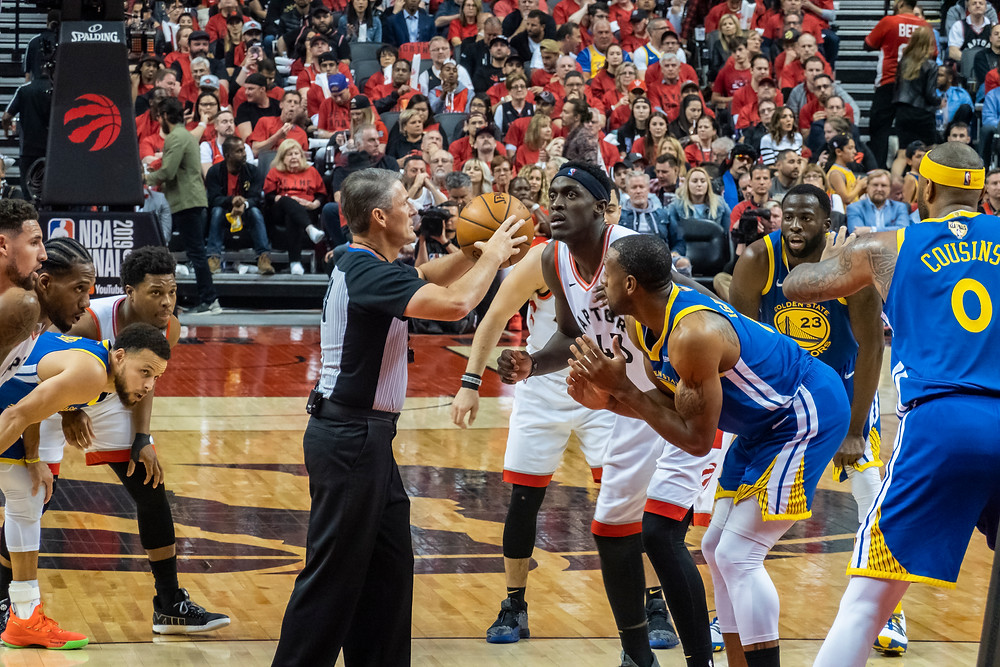 The Warriors and Raptors await a jump ball in the 2019 NBA Finals.