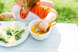 Baby girl eating her lunch in the garden