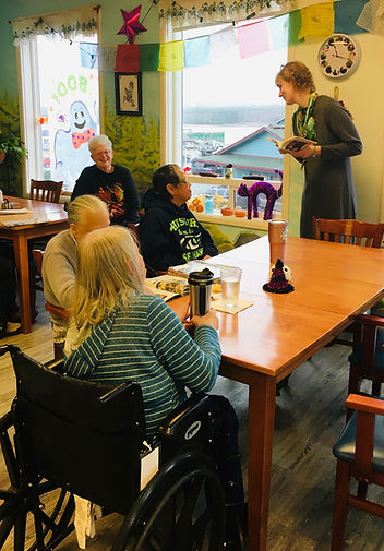 The seniors at Rendezvous Senior Day Services enjoy a read aloud from a Ketchikan Public Librarystaffer.