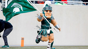 An image of Sparty running into the Spartan Stadium. He is carrying an MSU flag.