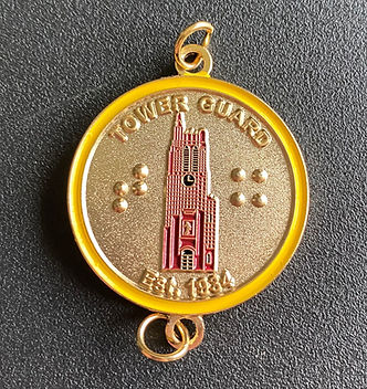 A photo of the Tower Guard medallion. It is golden with the Beaumont Tower engraved on it.