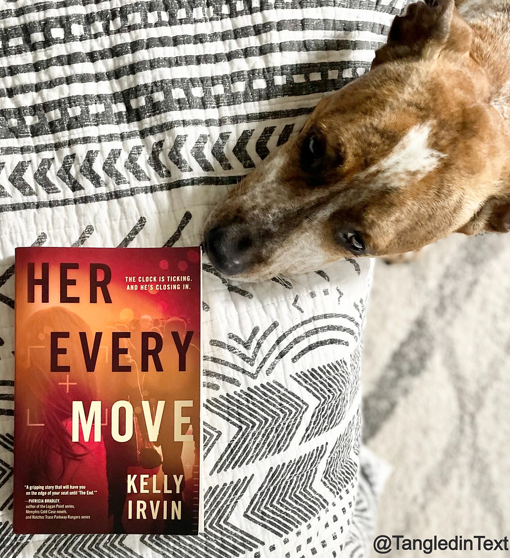 The book Her Every Move by Kelly Irvin with a dog smelling the cover