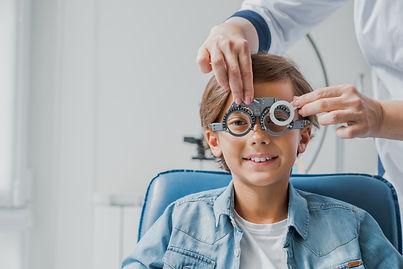 Smiling child boy in glasses checks eye