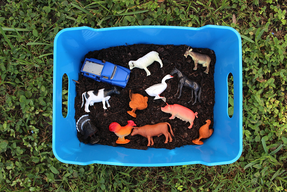 Blue plastic bin full of dirt and little farm animal toys