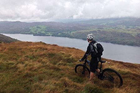 Biker stopped on hillside looking across lake