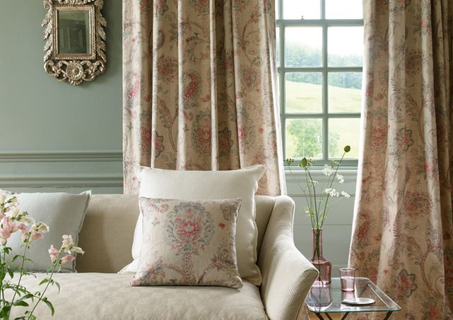 Colefax  & Fowler        With a muted palate of colour on the sofa the eye is cleverly drawn to the size and proportions of the room by the use of colour on the walls and  choice of patterned fabric for the curtains