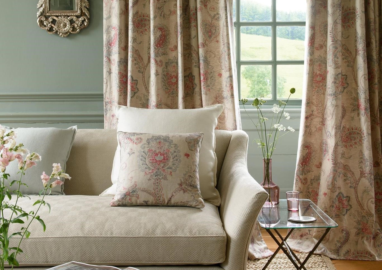Colefax & Fowler         With a muted palate of colour on the sofa the eye is cleverly drawn to the size and proportions of the room by the use of colour on the walls and pattern in the choice of curtains