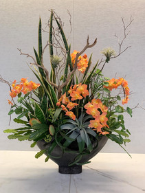 Custom floral arrangement with orchids, succulents, and wood for a corporate space