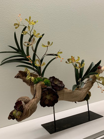 faux orchid and driftwood sculpture on metal stand