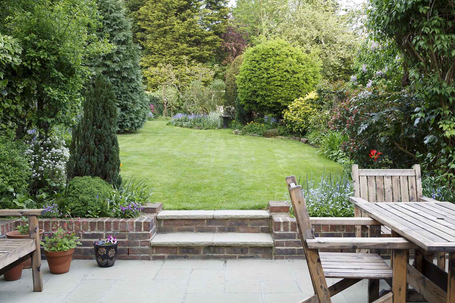 Garden patio with furniture and lawn in