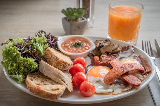 A tipikus angol reggeli: tükörtojás, kolbász, bacon, sült bab és paradicsom