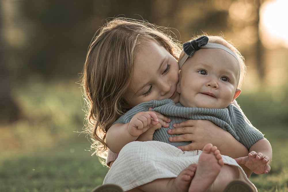 two sisters hugging at photo shoot in field