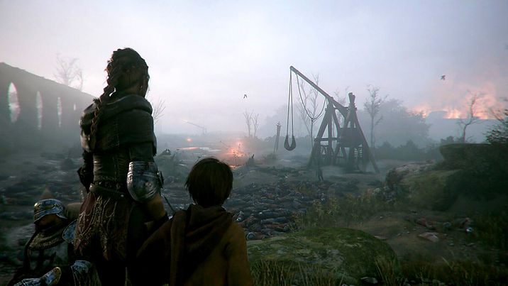 Post war scenery on the game A Plague Tale: Innocence, with a foggy landscape with many lifeless bodies and a trebuchet in the distance