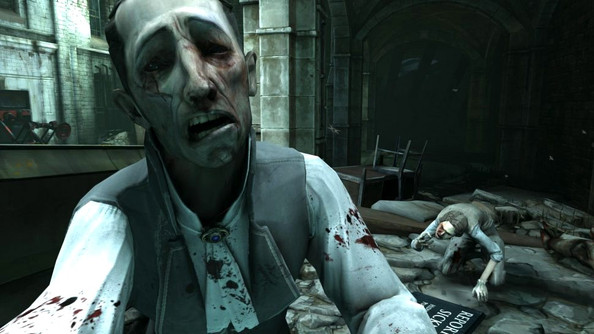 Sick people from the game Dishonored, with their clothing stained with blood in a closed urban area.