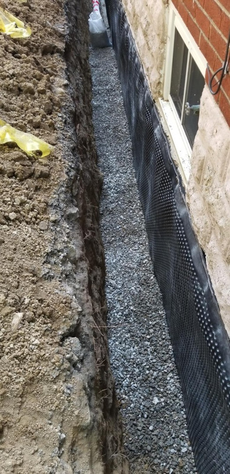 """Foundation waterproofing. Weeping tile covered with 3/4"""" clear stone"""