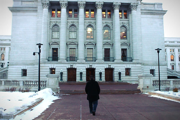 Apostle Scott standing in front of a state capitol building in the snow.