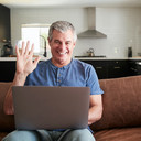 senior-man-video-calling-on-laptop-at-ho