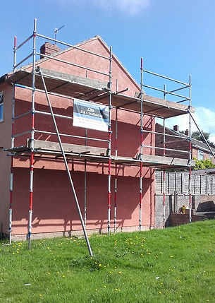 Scaffolding erected againstthe gable end of a pink house with the bottom half of the scaffolding being painted red and white like a barber pole