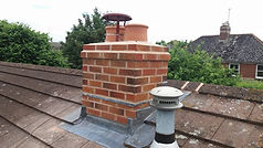 a newly re-built chimney with two terracotta chimney pots, silver gas flue and leadwork arount the chimney