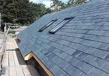 A slate roof surrounded by scaffolding boards with velux windows on a bright sunny day
