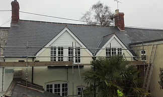 a property with scaffolding against its cream walls and a new slate roof.