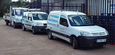 Three sign written vans with blue and black sign writing on
