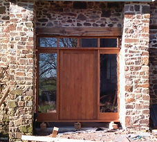 An attractive stained oak door with glazed windows either side and four panels at the top all surrounded by rustic brickwork