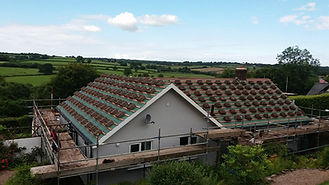 a bungalow in the exmoor countryside with stacks of roofing tiles laid out on a green felted roof with the scaffolding and views into the countryside surrounding
