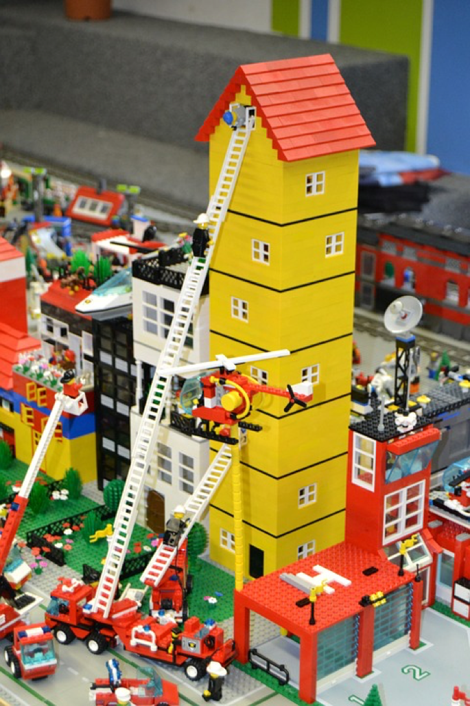 A Lego model of a building with roofing services applied to it