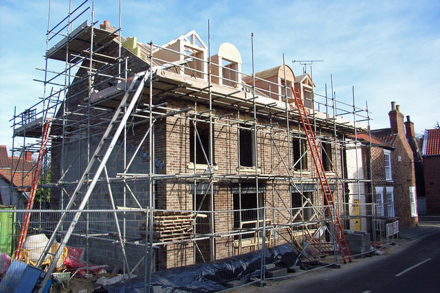 A new house being built with scaffolder, Tiverton working on it